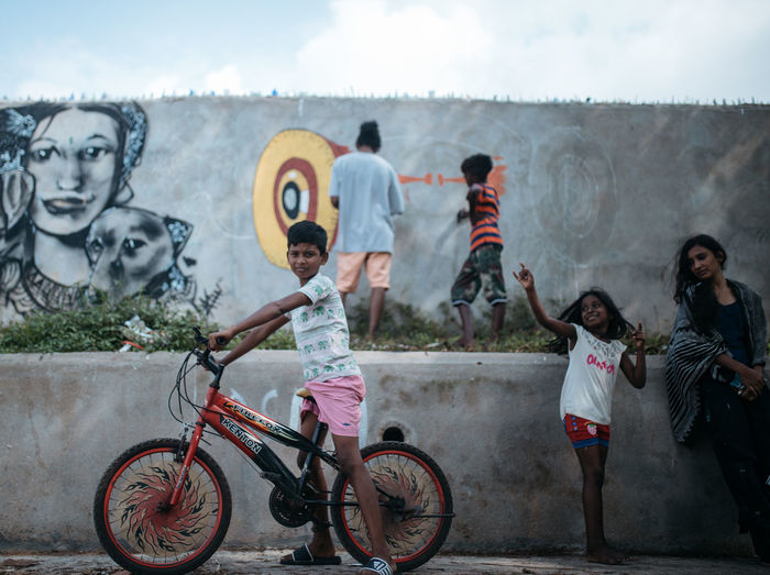 Children playing with bicycle against sky