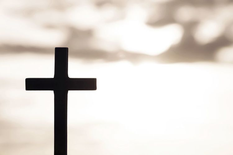 Close-up of cross against sky