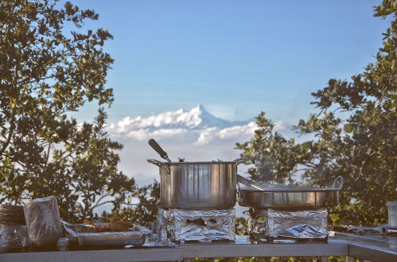 Cooking utensils on stove at table against sky
