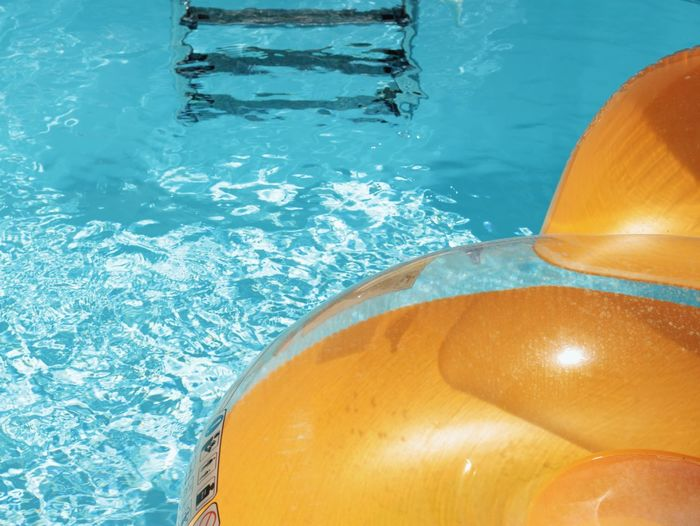 High angle view of yellow inflatable toy floating on swimming pool