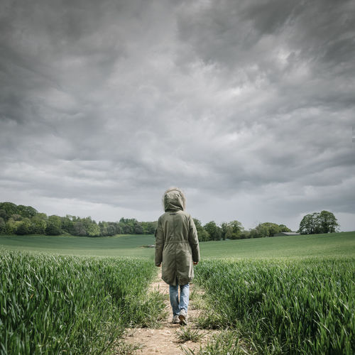 Rear view of a woman wearing a parka coat walking along a track in a wheat field with a stormy sky.