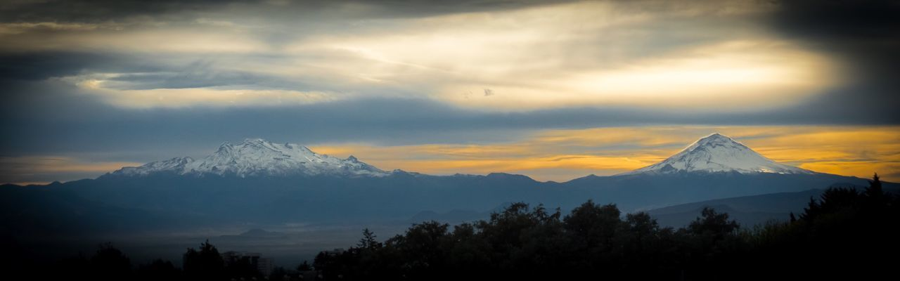 Panoramic Shot Of Snow Covered Mountains Against Sky During Sunset