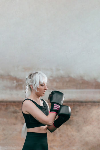 Woman with boxing gloves standing against wall