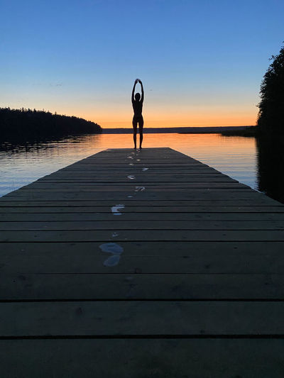 Silhouette woman standing on pier over lake against sky during sunset