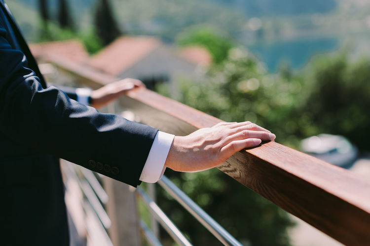 Midsection of businessman standing by railing