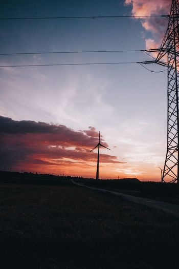 Silhouette electricity pylon on field against sky during sunset