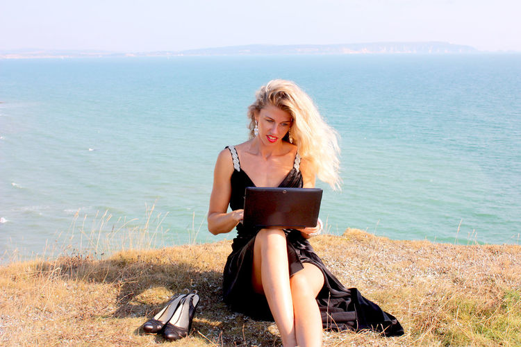 Beautiful Woman Using Laptop Against Sea On Sunny Day