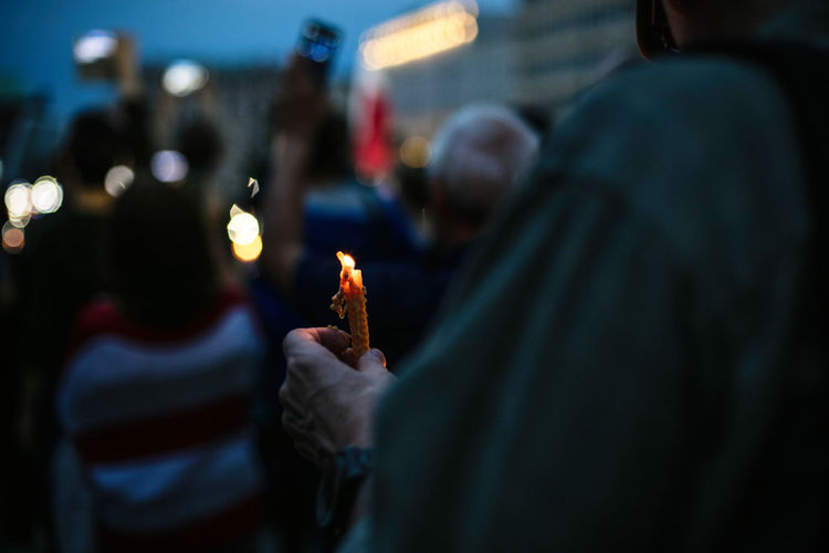 Midsection Of Protestor Holding Burning Candle During Protest At Night