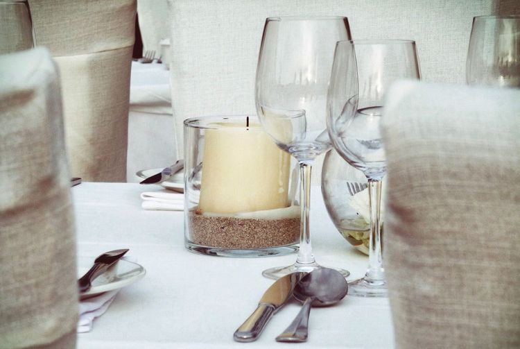 Close-up of tea light candles and wine glasses on table
