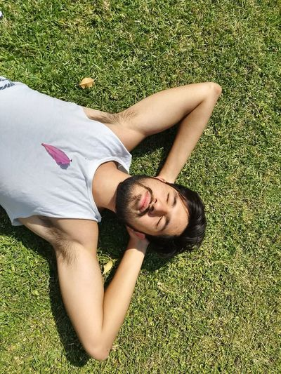 High Angle View Of Young Man Lying On Grassy Field