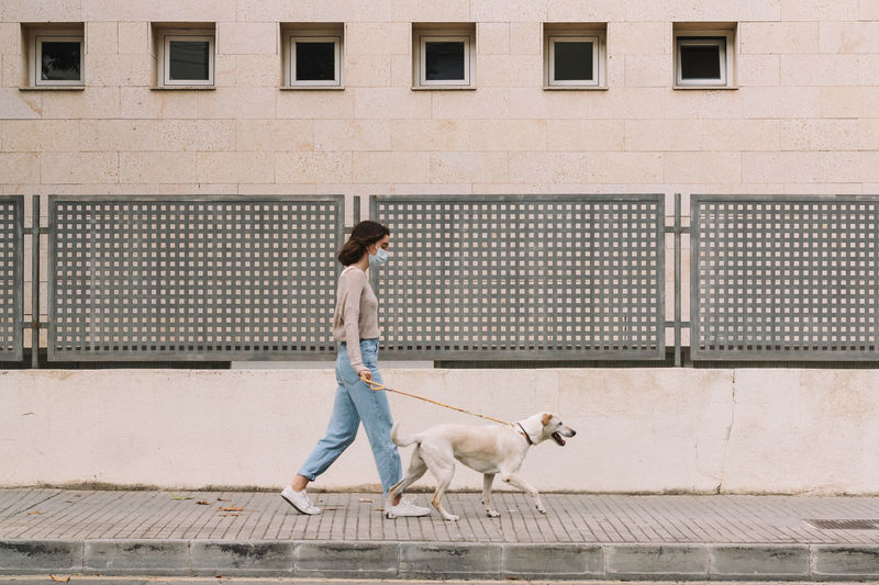 Full length of girl and dog walking on street against building