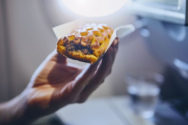 Traveling by airplane. Passenger enjoying snack in economy class during flight. Hand Holding Human Hand Food Freshness Close-up Real People Refreshment Drink Water Window Airplane Travel Journey Transportation People Eating Meal Snack Lunch Refreshment Flight Comfortable Passenger Lifestyles