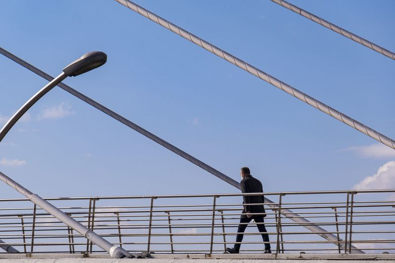 Low angle view of man standing by railing against sky