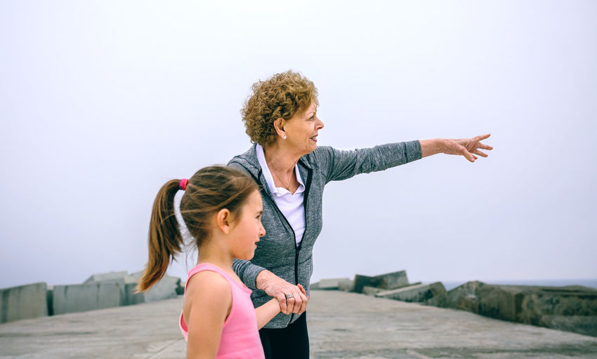 Grandmother and granddaughter standing on pier against sky