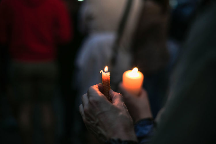 Cropped hands of protestors holding burning candle during protest at night