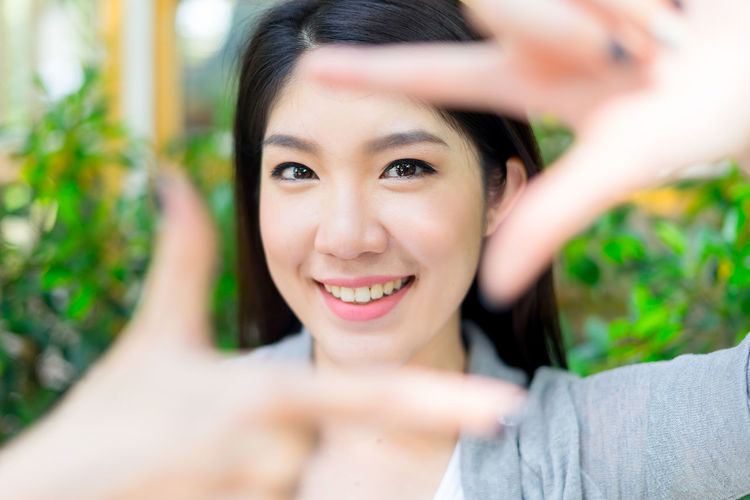 Portrait Of Smiling Young Woman Making Finger Frame