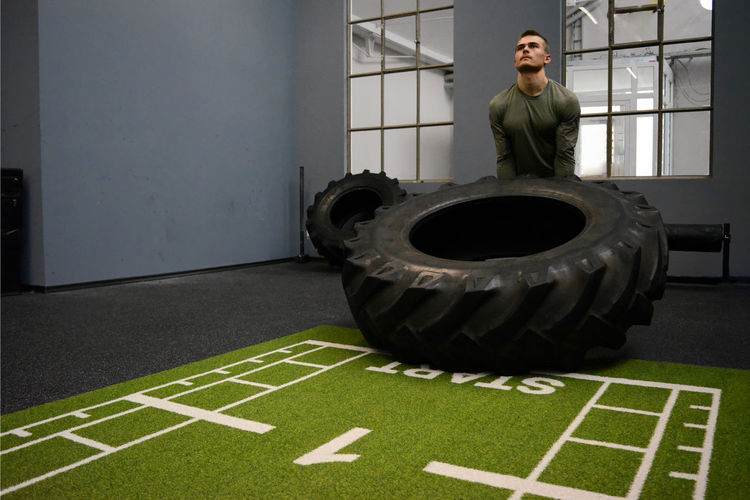 Young Man Exercising With Tire In Gym