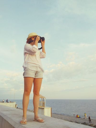 Full Length Of Young Woman Photographing Sea Against Sky