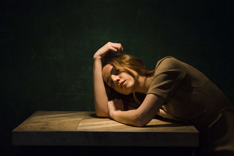 Portrait of woman sitting on table against black background
