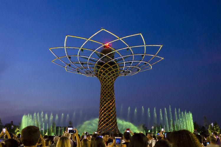 People on illuminated ferris wheel against blue sky