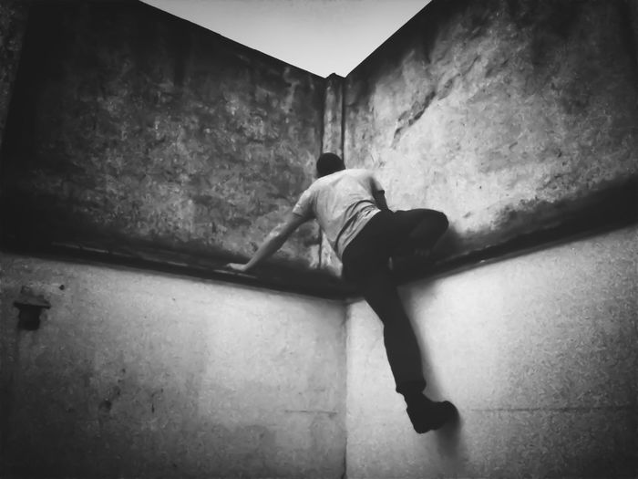 Rear view of man lying on wall