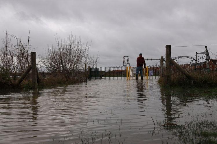 Full length of man standing on wet shore against sky