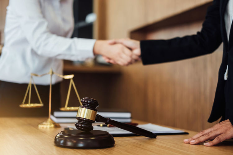 Cropped image of judge shaking hands with client on table