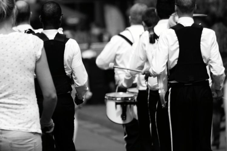 Rear view of marching band walking on street in city