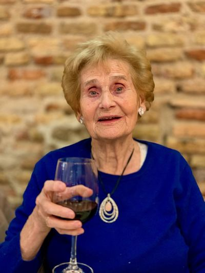Portrait of senior woman having drink in wineglass against brick wall