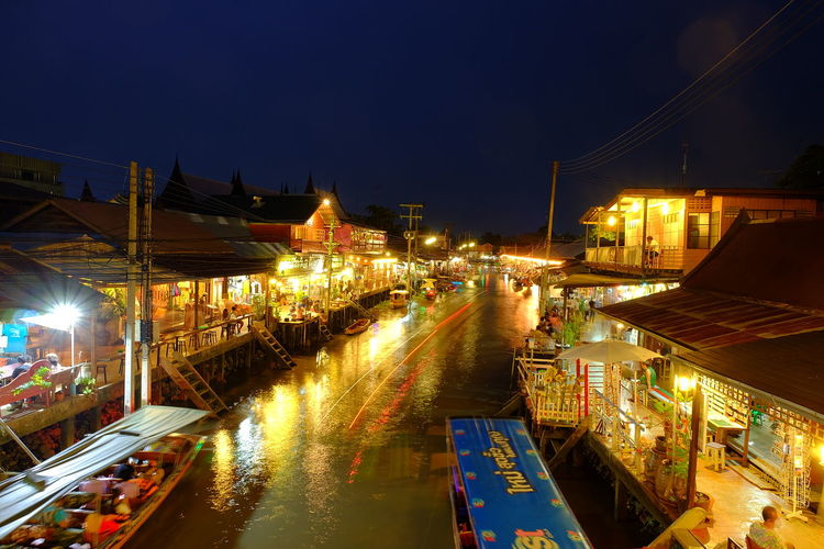 Boats on canal at illuminated floating market in city during night