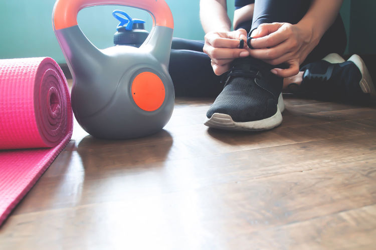 Sport and fitness lifestyle with healthy woman Home Lifestyle Sport Shoes Adult Body Part Day Fitness Flooring Gym Hand Healthy Healthy Lifestyle Human Body Part Human Leg Kettlebell  Leisure Activity Lifestyles People Real People Shoe Sitting Sport Women Wood Workout