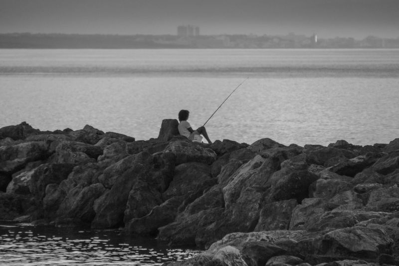 Rear view of man fishing while sitting on rocks against sea