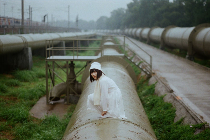 Portrait Of Woman Crouching On Water Pipe
