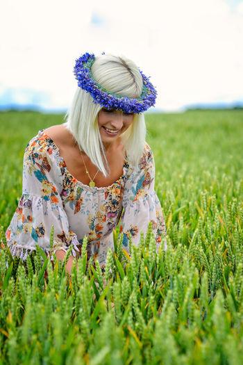 beautiful woman wearing floral headwear at field