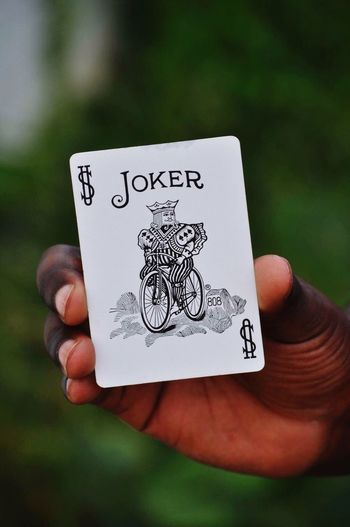 Cropped Hand Of Man Showing Joker Card