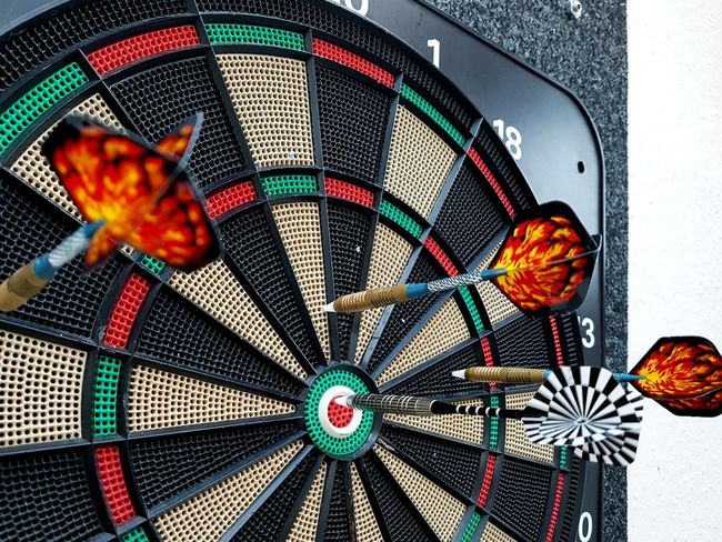 Close up of Dart Arrows stuck in Dart Board. One arrow right in the middle... Selected For Partner Dart Competition Competitive Sport Competition Dartboard Dart Arrow Close Up Close Up Dart Board Multi Colored Gambling Pool Ball Chance Leisure Games Fanned Out Close-up Concentric