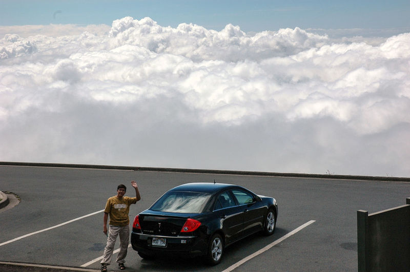 Man Standing By Car At Parking Lot Against Cloudy Sky