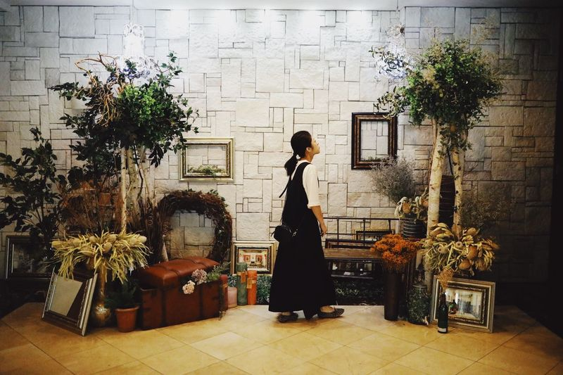 Side view of woman standing against plants