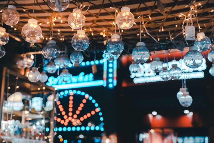 Low angle view of illuminated lanterns hanging in store