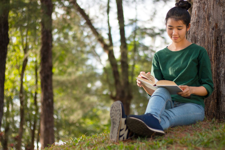 Full length of young woman reading book while leaning on tree at park