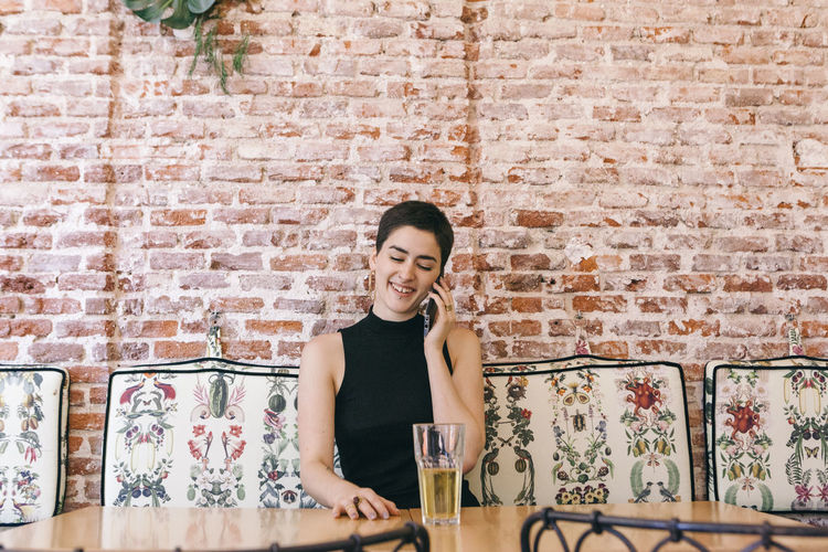 Smiling young woman talking over smart phone while sitting against brick wall in cafe