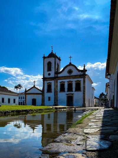 Church by building against blue sky