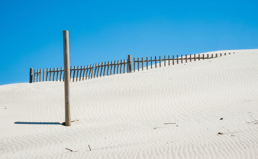 Wooden posts on beach against clear blue sky