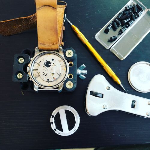 Directly above shot of wristwatch being repaired on table
