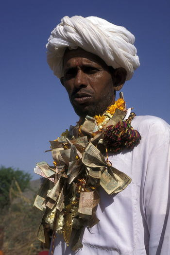 Man Wearing Necklace Made By Paper Currency