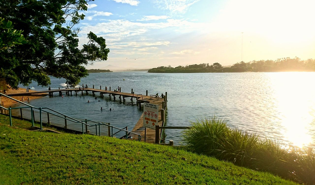tree, nature, scenics, beauty in nature, tranquil scene, water, tranquility, grass, sky, outdoors, no people, green color, growth, lake, built structure, sunset, day, architecture