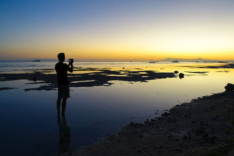 Silhouette of man standing on beach at sunset