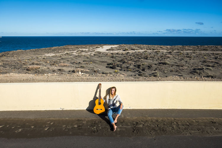 rebel and youth concept for beautiful young woman sit down with no shoes and ocean in background Adult barefoot Beach Beautiful Woman Blue Day Full Length Guitars Horizon Over Water Landscape Musician Nature Ocean One Person One Woman Only Outdoors People Sand Sea Sky Summer Tenerife Women Young Girl Youth Culture