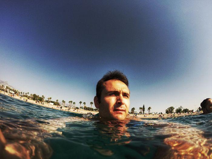 Man looking away while swimming in sea