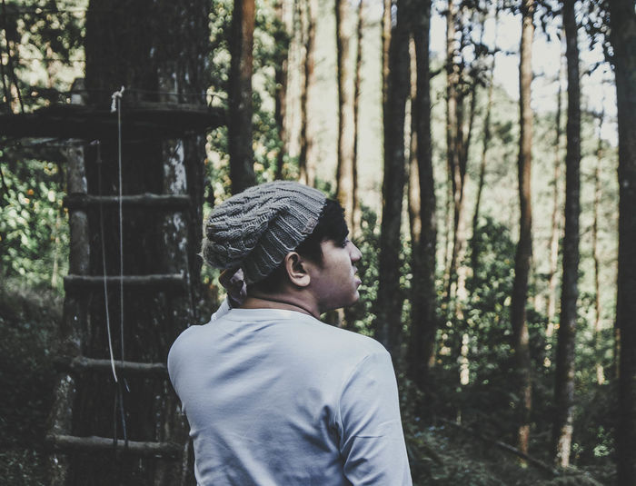 Side view of young man standing against trees in forest